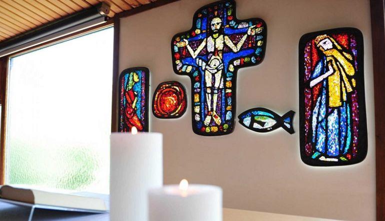 Foto von brennenden Kerzen und Blick auf bunte Glasbilder, in der Mitte Jesus am Kreuz (Foto epd uschmann)